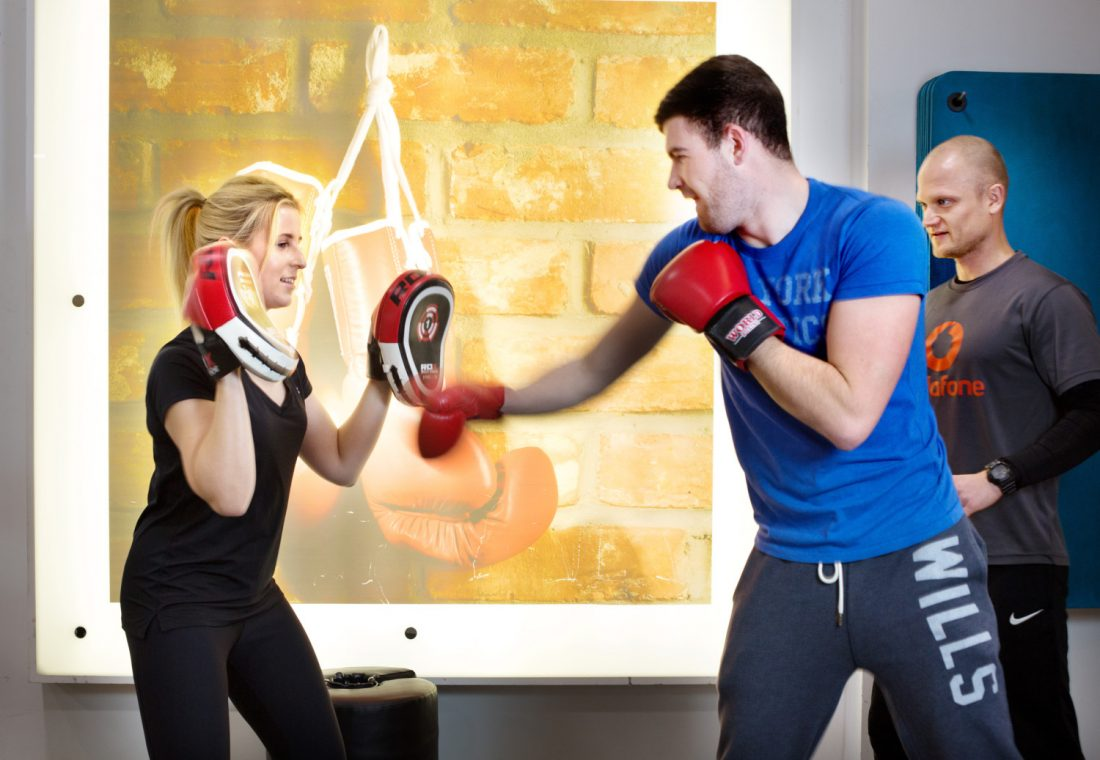 Woman and man spar in the gym.