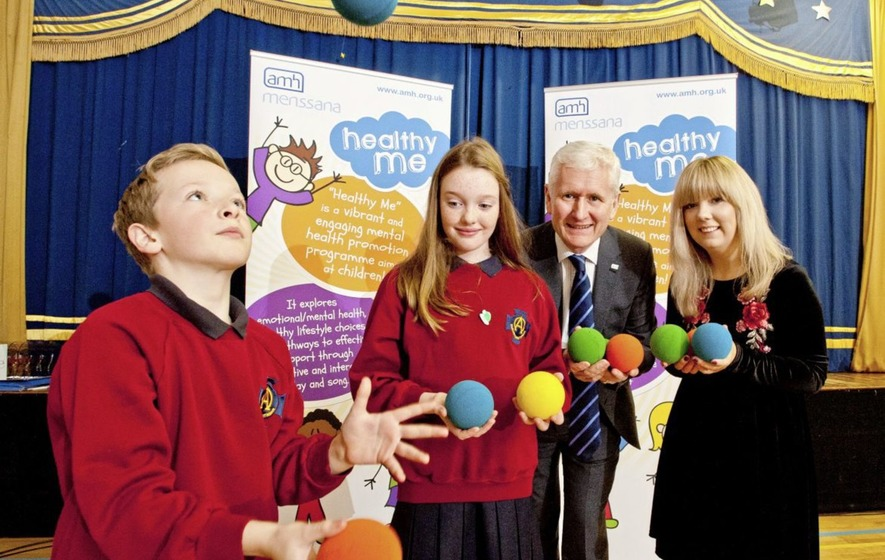 Two children juggling balls and an adult couple assisting them.